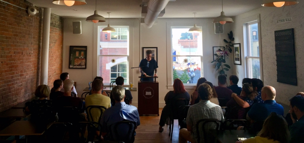 Matthew Kirkpatrick reading from his book to an audience at the Literati Bookstore